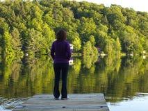 Frau, die an einem See steht Stockfotografie