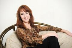 Frau, die in einem Stuhl sitzt Lizenzfreie Stockfotografie