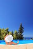 Frau, die in einem Swimmingpool mit Cocktail sich entspannt lizenzfreie stockbilder
