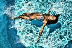 Frau, die in einem Swimmingpool sich entspannt Stockbilder