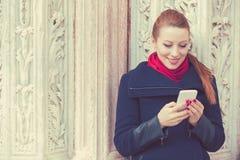 Frau, die an einem Telefon simst stockfotos