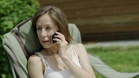 Frau, die an einem Telefon spricht stock footage