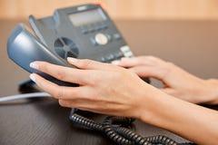 Frau, die an einem Telefon wählt Lizenzfreie Stockfotos