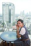 Frau, die an einem Tisch sitzt Lizenzfreies Stockfoto