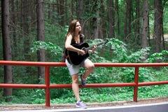 Frau, die in einem Wald auf einer Straßenseite auf einer schwarzen Akustikgitarre singt stockbilder