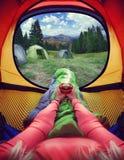 Frau, die in einem Zelt mit Kaffee, in der Ansicht von Bergen und im Himmel liegt Lizenzfreies Stockfoto