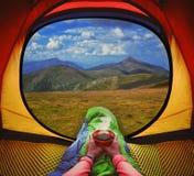 Frau, die in einem Zelt mit Kaffee, in der Ansicht von Bergen und im Himmel liegt Stockfotos
