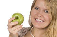 Frau, die einen Apfel anhält Lizenzfreie Stockfotografie