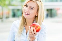 Frau, die einen Apfel hält Lizenzfreies Stockbild