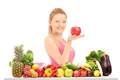 Frau, die einen Apfel hält und voll hinter einer Tabelle von vegate aufwirft Stockfotografie
