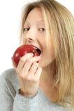 Frau, die einen Apfel isst Lizenzfreies Stockbild