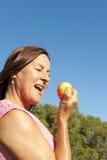 Frau, die einen Apfel isst Stockfotografie