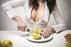 Frau, die einen Apfel schneidet Lizenzfreie Stockfotos