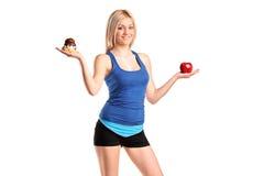 Frau, die einen Apfel und eine Scheibe des Kuchens anhält lizenzfreie stockfotografie