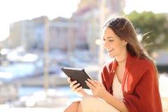 Frau, die einen aufpassenden Medieninhalt der Tablette verwendet Lizenzfreies Stockfoto