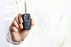 Frau, die einen Autoschlüssel auf weißen Hintergründen hält lizenzfreie stockbilder