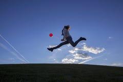 Frau, die einen Ballon hält und draußen springt Lizenzfreies Stockbild