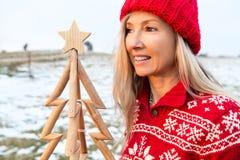 Frau, die einen Bauholz Weihnachtsbaum, Weihnachtsjahreszeit, Weihnachtsim juli Themen hält stockfotografie