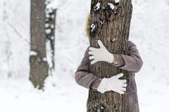 Frau, die einen Baum im Winterwald umarmt Liebevolle Natur Lizenzfreies Stockfoto