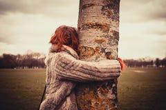 Frau, die einen Baum umarmt Stockbild