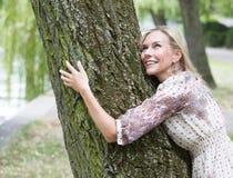 Frau, die einen Baum umarmt Stockfoto