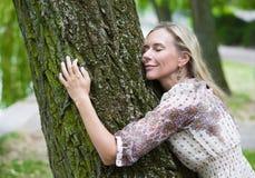 Frau, die einen Baum umarmt Stockfotografie