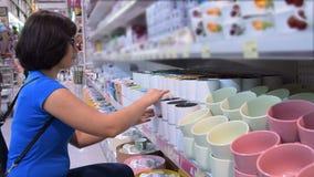 Frau, die einen Becher im Speicher kauft stock footage