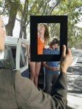 Frau, die einen bereitstehenden Packwagen der jungen Paare auf einer Autoreise gestaltet Stockbilder