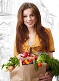 Frau, die einen Beutel voll von der gesunden Nahrung anhält. Lizenzfreies Stockbild