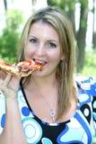 Frau, die einen Bissen der Pizza nimmt Stockbild