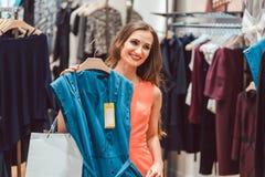 Frau, die einen blauen Kleiderspeicher in Mode kaufend erwägt lizenzfreies stockfoto