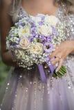 Frau, die einen Blumenstrauß der Blumen anhält stockfoto