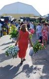 Frau, die einen Blumenstrauß durch einen spanischen Markt trägt Lizenzfreies Stockfoto