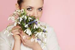 Frau, die einen Blumenstrauß von Schneeglöckchen hält stockbild
