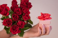 Frau, die einen Blumenstrauß von roten Rosen und von Geschenk hält lizenzfreies stockbild