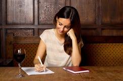 Frau, die einen Brief in einer Stange schreibt Lizenzfreie Stockfotografie