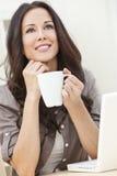 Frau, die einen Computer verwendet und Tee oder Kaffee trinkt Lizenzfreie Stockbilder