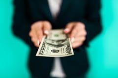 Frau, die einen 100 Dollarschein hält Lizenzfreie Stockbilder