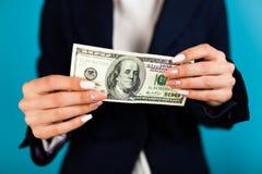 Frau, die einen 100 Dollarschein hält Stockfoto