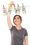 Frau, die einen Dollarschein vom Seil nimmt Lizenzfreies Stockfoto
