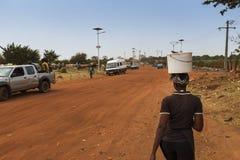 Frau, die einen Eimer auf ihrem Kopf trägt und entlang einen Schotterweg auf den Stadtränden der Stadt von Bissau, in Guinea-Biss stockfotografie