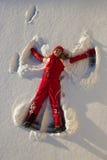 Frau, die einen Engel auf Schnee bildet Lizenzfreies Stockbild