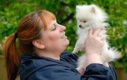 Frau, die einen entzückenden weißen Pomeranian Welpen anhält Stockfotos