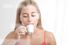 Frau, die einen Espresso an einer Kaffeestube trinkt Lizenzfreies Stockbild