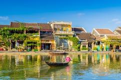 Frau, die einen Fluss auf einem Boot in Hoi An kreuzt Lizenzfreies Stockfoto