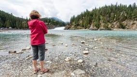 Frau, die einen Fluss bereitsteht Stockfotos