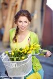 Frau, die einen Frühlingsrock wie der Weinlesestift-oben hält Fahrrad trägt lizenzfreies stockfoto