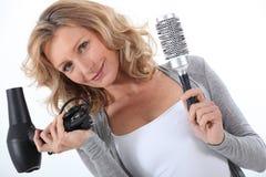 Frau, die einen Haartrockner anhält Stockfoto