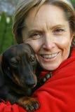 Frau, die einen Hund anhält Lizenzfreie Stockbilder