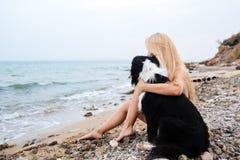 Frau, die einen Hund auf dem Strand sitzt und umarmt Stockbilder
